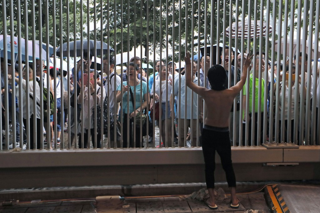 A pro-democracy protester, front, argue with pro-China's supporters during a rally outside Legislative Council Complex in Hong Kong, Sunday, June 30, ...
