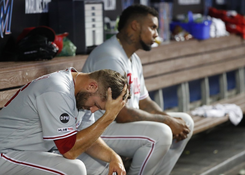 Philadelphia Phillies relief pitchers Adam Morgan, foreground, and Juan Nicasio sit in the dugout during the seventh inning of a baseball game against...