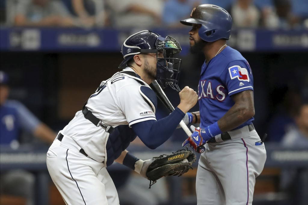 Tampa Bay Rays catcher Travis d'Arnaud, left, celebrates a strike out of Texas Rangers' Delino DeShields, right, during the sixth inning of a baseball...