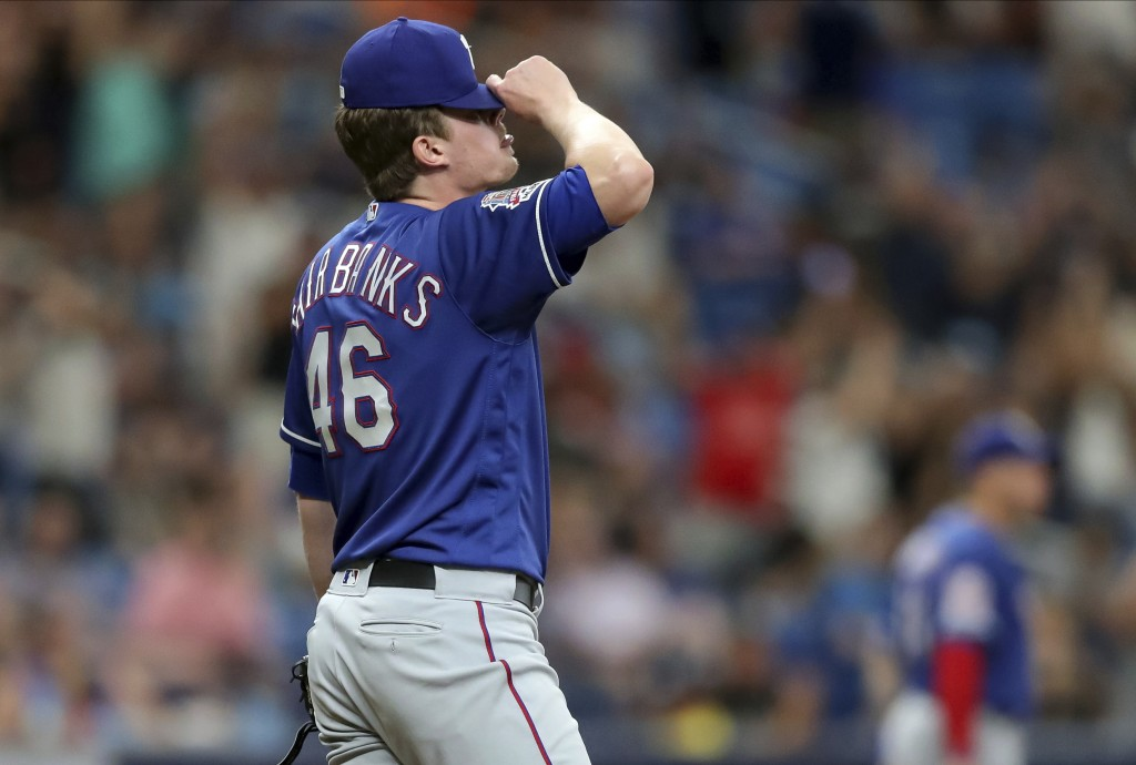 Texas Rangers relief pitcher Peter Fairbanks reacts after giving up home runs on back-to-back pitches against the Tampa Bay Rays during the seventh in...