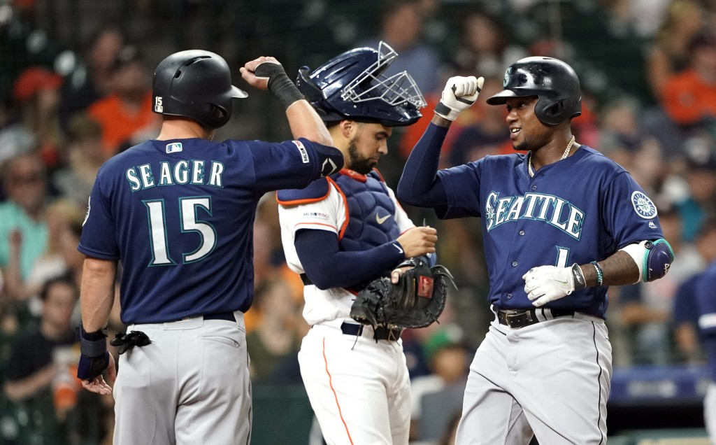 Seattle Mariners' Tim Beckham (1) celebrates with Kyle Seager (15) after both scored on Beckham's home run as Houston Astros catcher Robinson Chirinos...