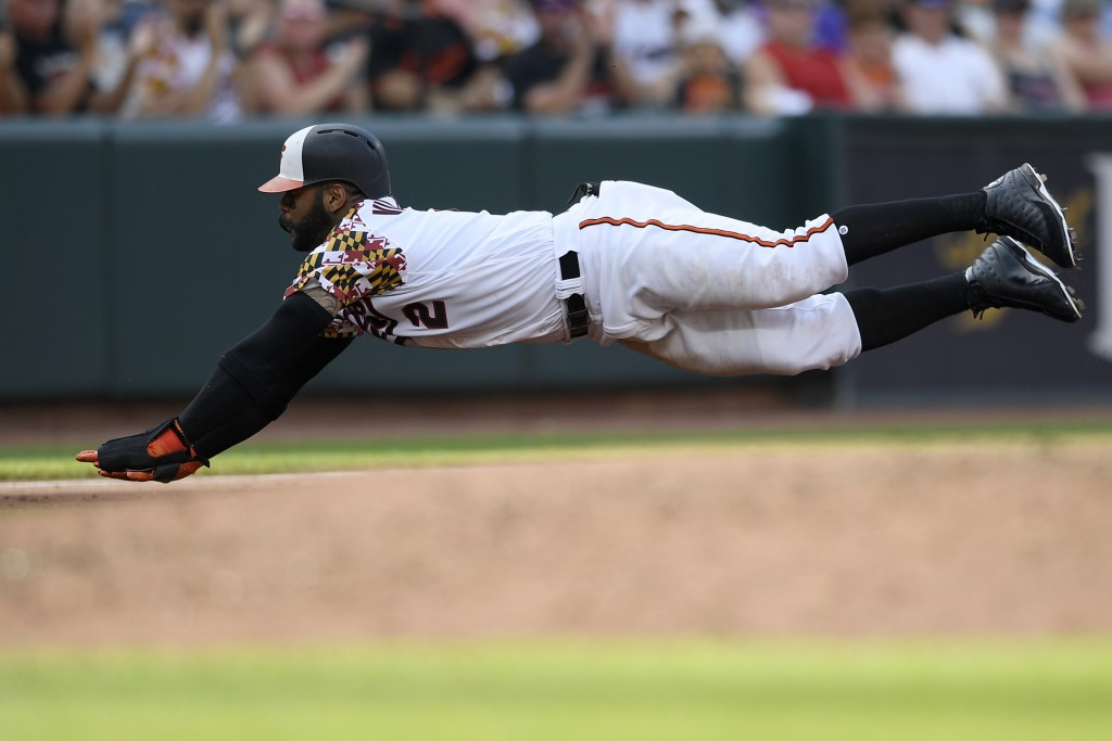 Baltimore Orioles' Jonathan Villar dives towards third on a single by Trey Mancini during the third inning of the team's baseball game against the Cle...