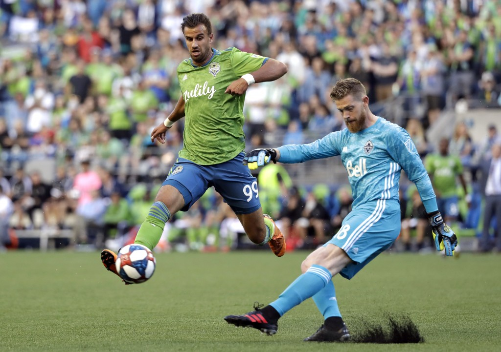 Vancouver Whitecaps goalie Zac MacMath, right, kicks the ball just past Seattle Sounders' Justin Dhillon in the first half of an MLS soccer match Satu...