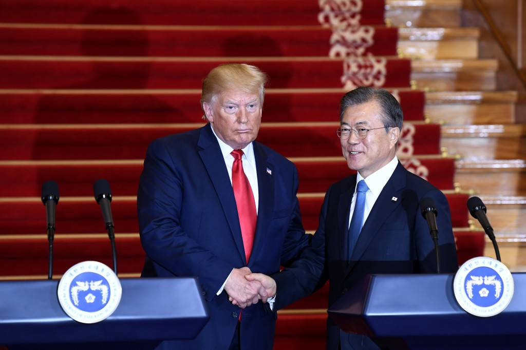 President Donald Trump, left, and South Korean President Moon Jae-in shake hands following their news conference at the Blue House in Seoul, Sunday, J...