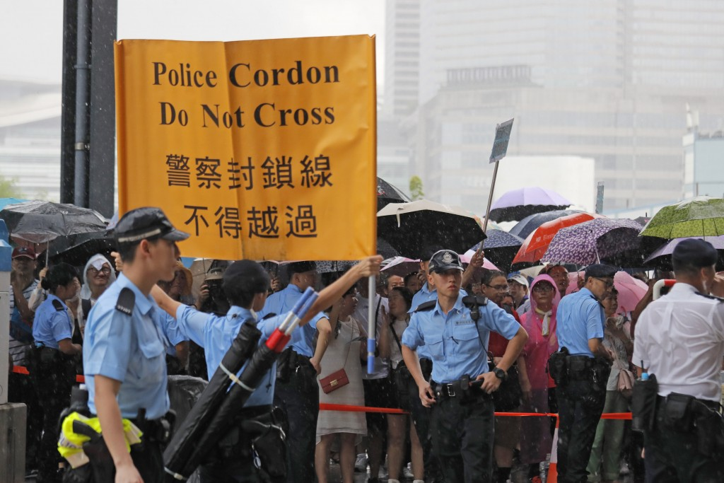 Police officers shows a warning banner to pro-China's supporters during a rally outside Legislative Council Complex in Hong Kong, Sunday, June 30, 201...