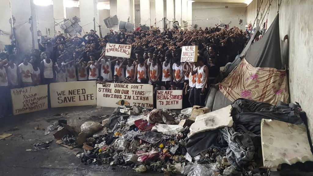 In this May 21, 2019 photo provided by an African migrant, hundreds of migrants stage a protest in a detention center in the town of Zintan, western L...