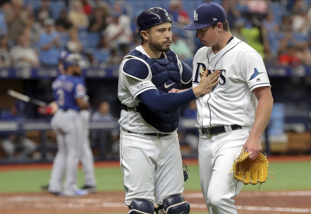 Tampa Bay Rays catcher Travis d'Arnaud congratulates starting pitcher Brendan McKay after striking out Texas Rangers' Delino DeShields during the sixt...