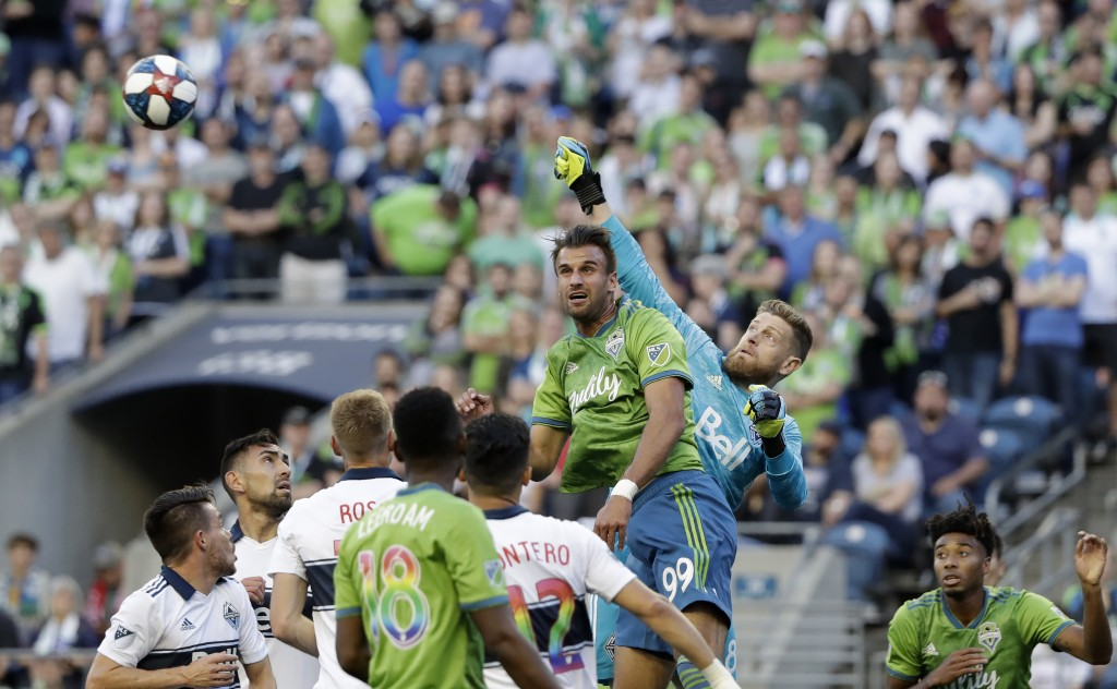 Vancouver Whitecaps goalie Zac MacMath, center right, taps away the ball behind Seattle Sounders' Justin Dhillon during the first half of an MLS socce...