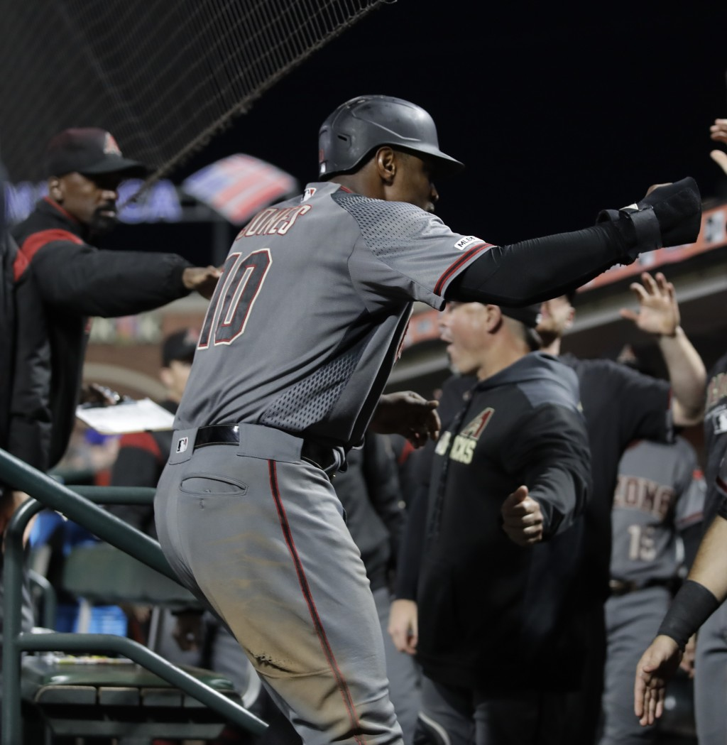 Arizona Diamondbacks' Adam Jones (10) returns to the dugout after scoring against the San Francisco Giants during the seventh inning of a baseball gam...