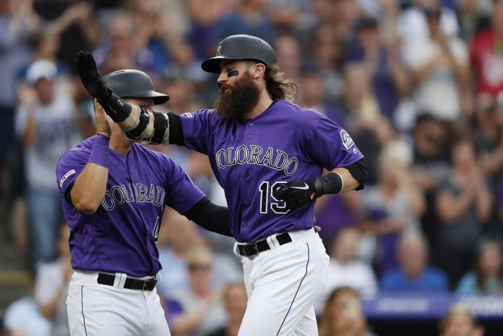 Colorado Rockies' Pat Valaika, left, congratulates Charlie Blackmon who crosses home plate after hitting a two-run home run off Los Angeles Dodgers st...