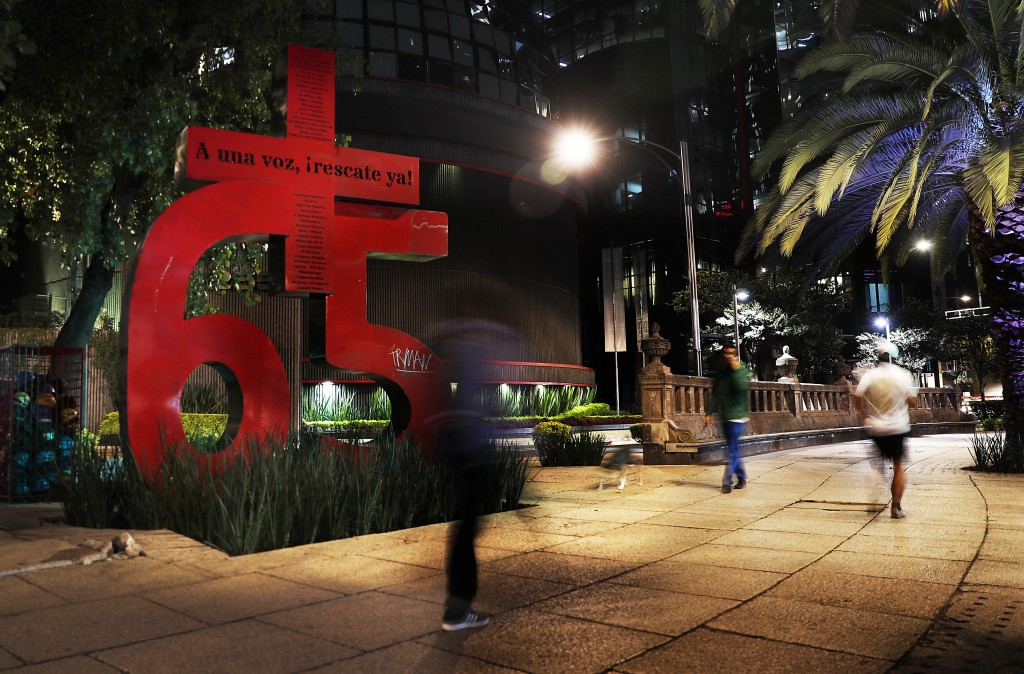 In this June 18, 2019 photo, pedestrians walk past the Mexican Stock Exchange where activists have erected a sculpture of a bright red number 65 that ...