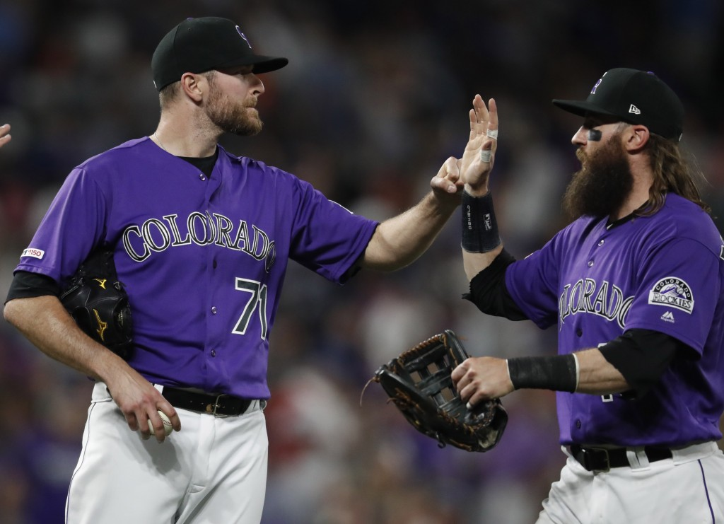 Colorado Rockies relief pitcher Wade Davis, left, congratulates right fielder Charlie Blackmon after the ninth inning of a baseball game against the L...