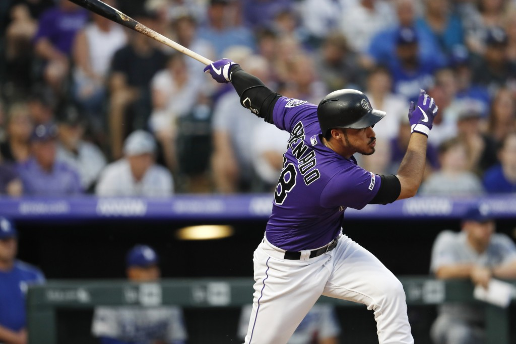 Colorado Rockies' Nolan Arenado follows the flight of his RBI-single off Los Angeles Dodgers starting pitcher Clayton Kershaw in the sixth inning of a...