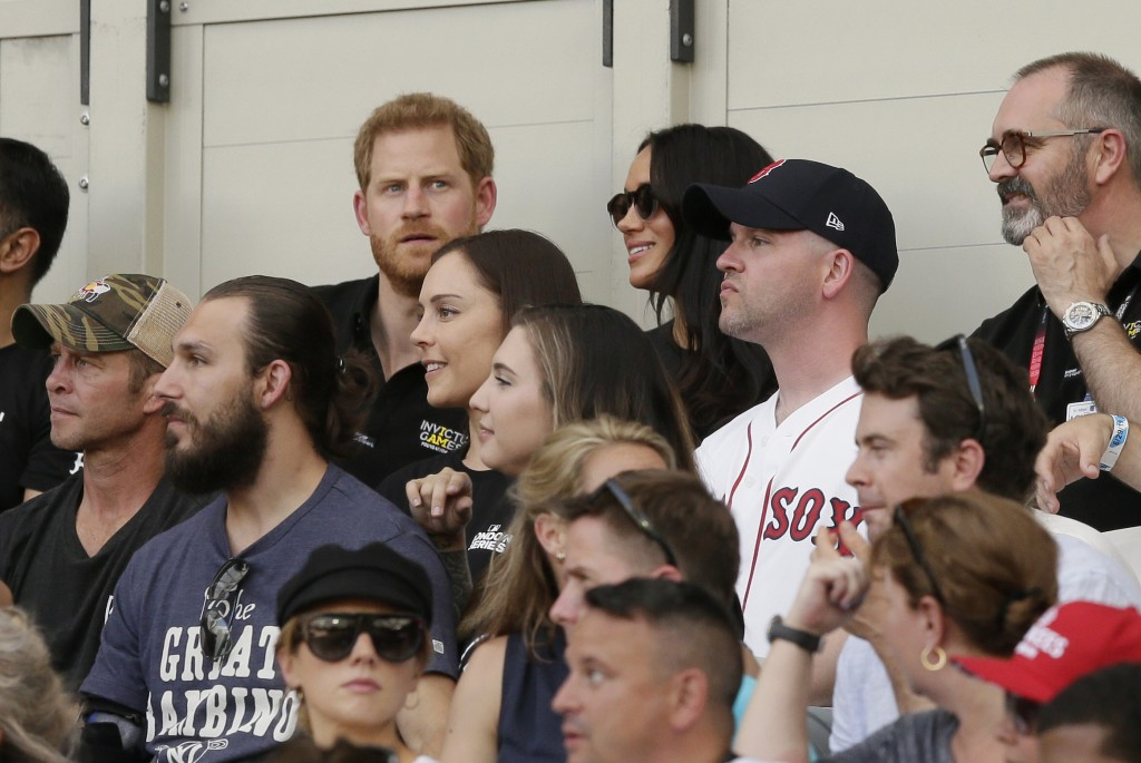 Britain's Prince Harry, top left, and Meghan, Duchess of Sussex, watch during the first inning of a baseball game between the Boston Red Sox and the N...