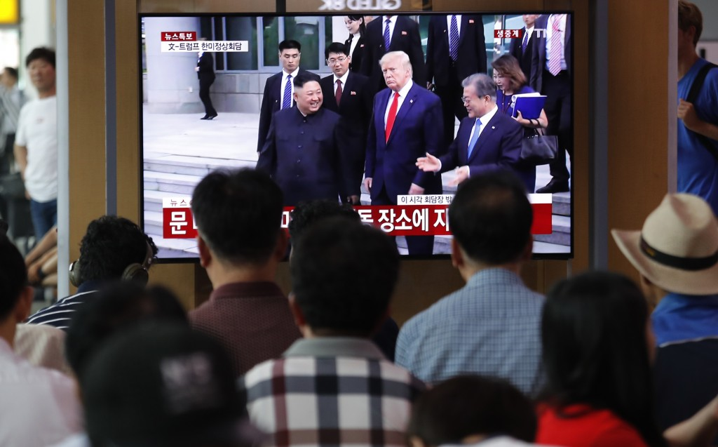 People watch a TV screen showing the U.S. President Donald Trump, center, North Korean leader Kim Jong Un and South Korean President Moon Jae-in, cent...