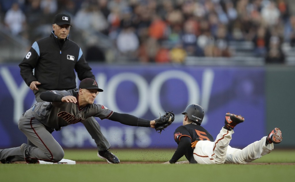 Arizona Diamondbacks' Nick Ahmed, front left, tags out San Francisco Giants' Mike Yastrzemski, right, in the first inning of a baseball game Saturday,...