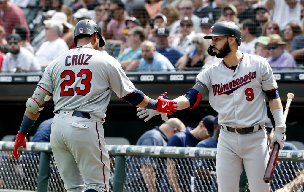 Minnesota Twins' Nelson Cruz (23) is greeted by teammate Marwin Gonzalez (9) after hitting a two-run home run against the Chicago White Sox during the...