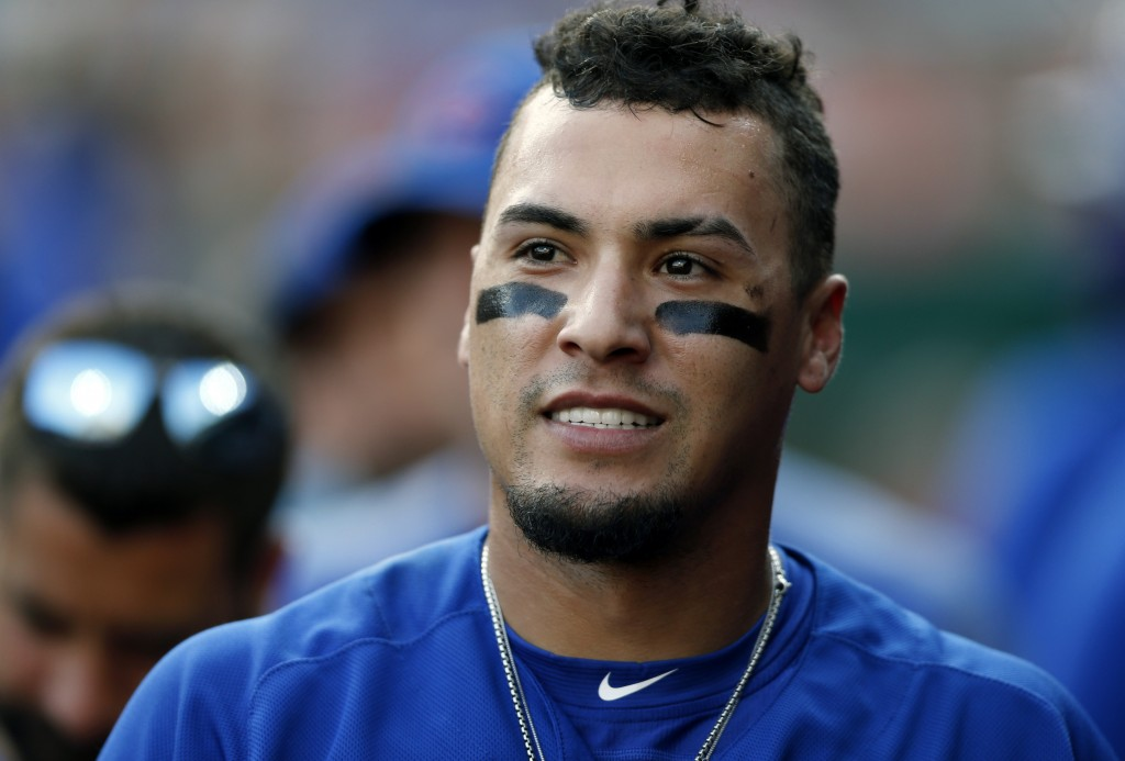 Chicago Cubs' Javier Baez smiles in the dugout after hitting a grand slam off Cincinnati Reds relief pitcher Jared Hughes during the eighth inning of ...