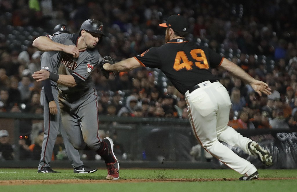 Arizona Diamondbacks' Tim Locastro, left, is tagged out by San Francisco Giants' Sam Dyson (49) during the seventh inning of a baseball game Saturday,...