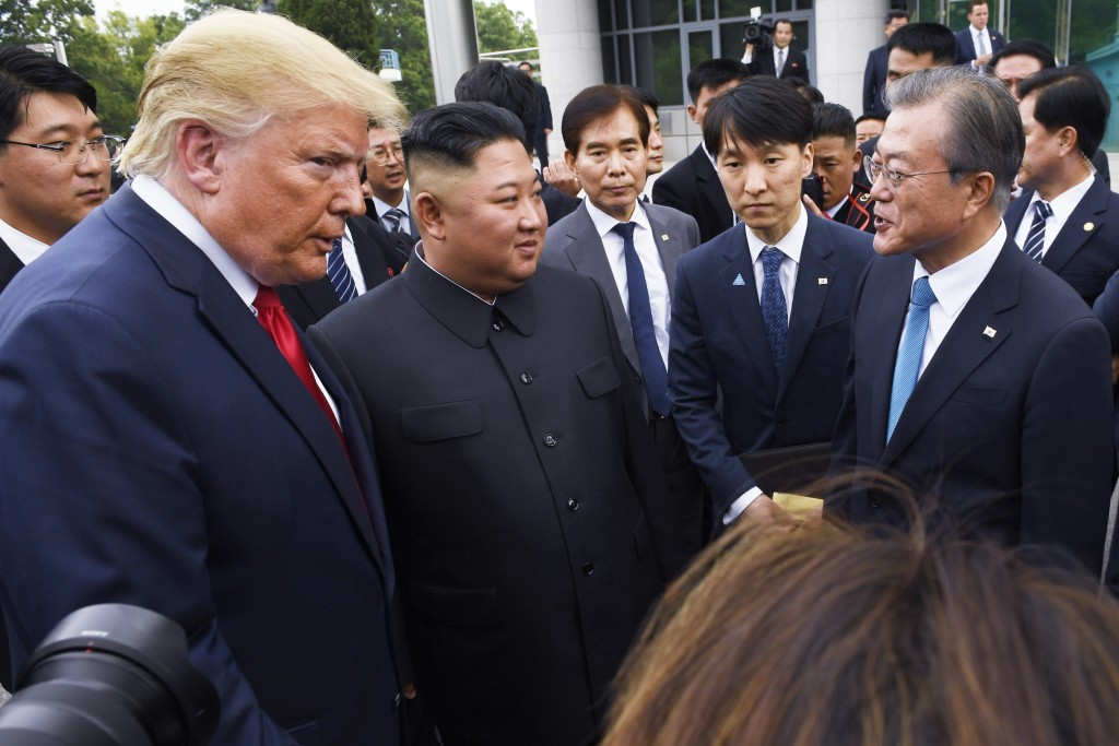 President Donald Trump meets with North Korean leader Kim Jong Un and South Korean President Moon Jae-in, right, at the border village of Panmunjom in...