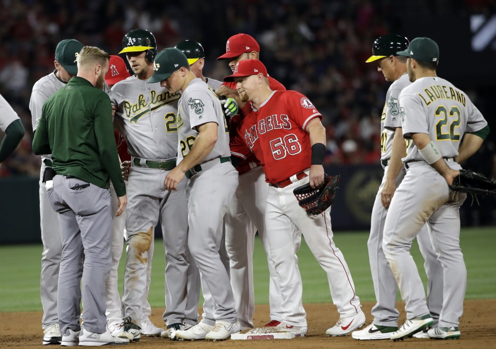 Oakland Athletics' Stephen Piscotty, third from left, is helped off the field after an injury during the sixth inning of the team's baseball game agai...