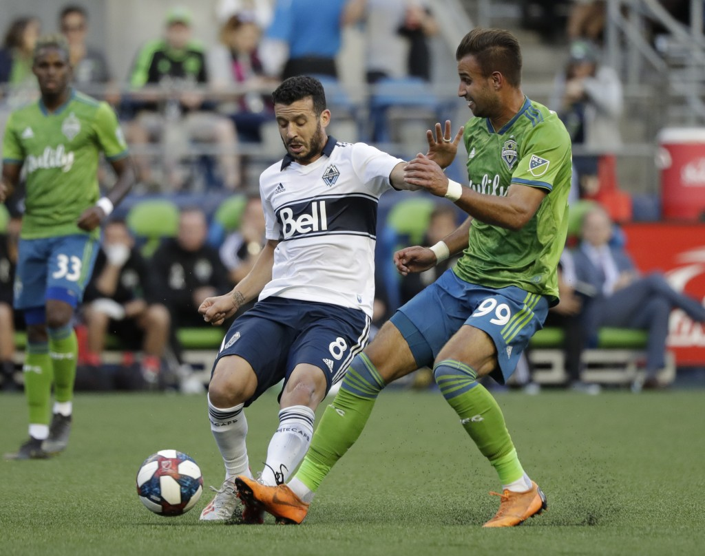 Vancouver Whitecaps' Felipe Martins (8) tries to control the ball in front of Seattle Sounders' Justin Dhillon in the first half of an MLS soccer matc...
