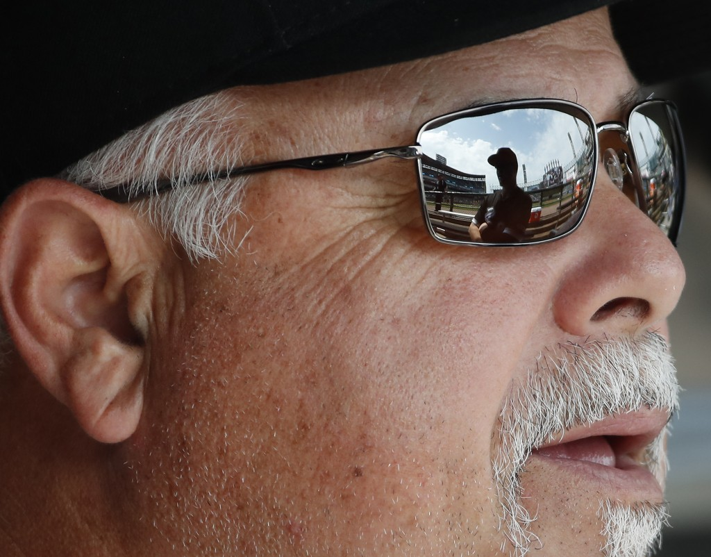 Chicago White Sox manager Rick Renteria listen to his catcher Zack Collins, reflected in his glasses, before a baseball game between the Minnesota Twi...