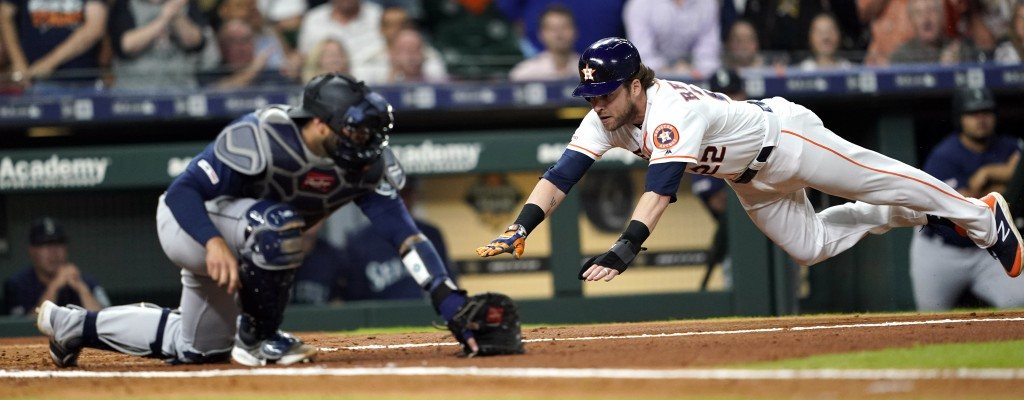 Houston Astros' Josh Reddick (22) dives past Seattle Mariners catcher Omar Narvaez to score during the second inning of a baseball game Saturday, June...