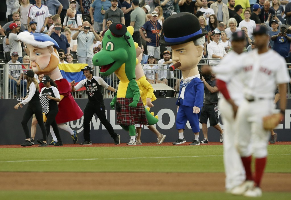 Characters including from left, King Henry VIII, the Loch Ness monster and Winston Churchill participate in a mascot race during a baseball game betwe...