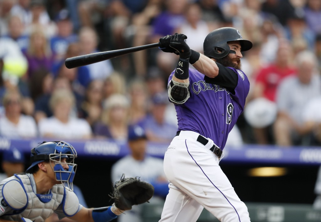 Colorado Rockies' Charlie Blackmon, right, follows the flight of his two-run home run with Los Angeles Dodgers catcher Austin Barnes in the third inni...