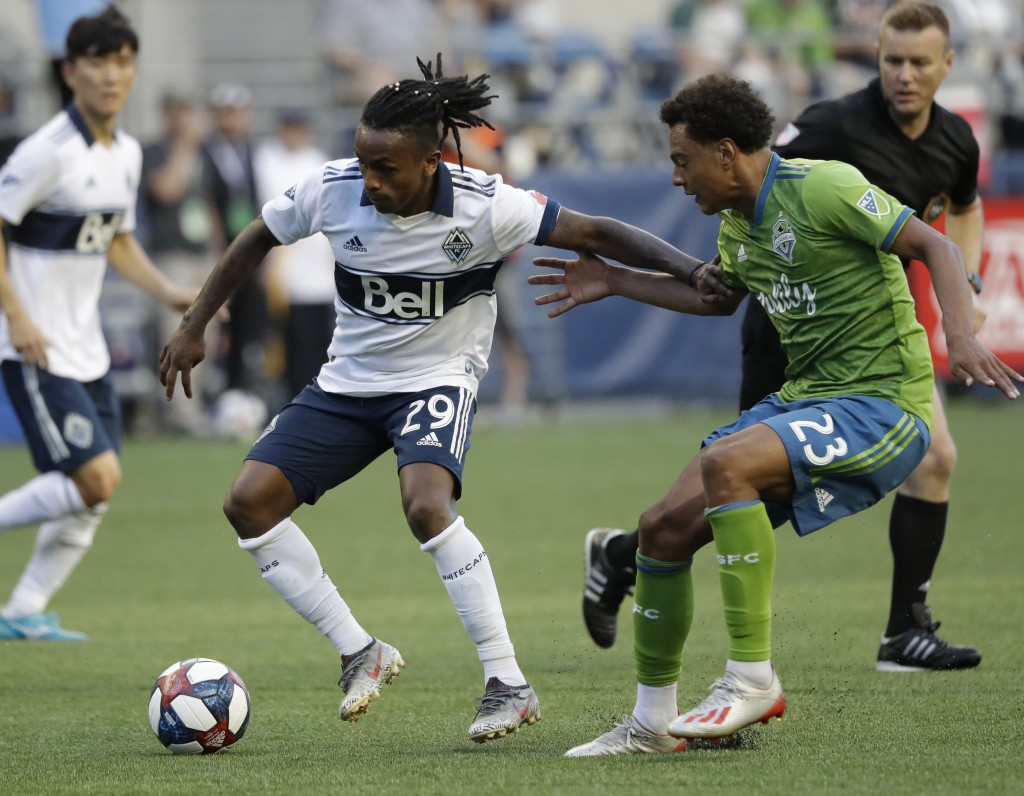 Vancouver Whitecaps' Yordi Reyna (29) tries to control the ball in front of Seattle Sounders' Henry Wingo (23) during the first half of an MLS soccer ...