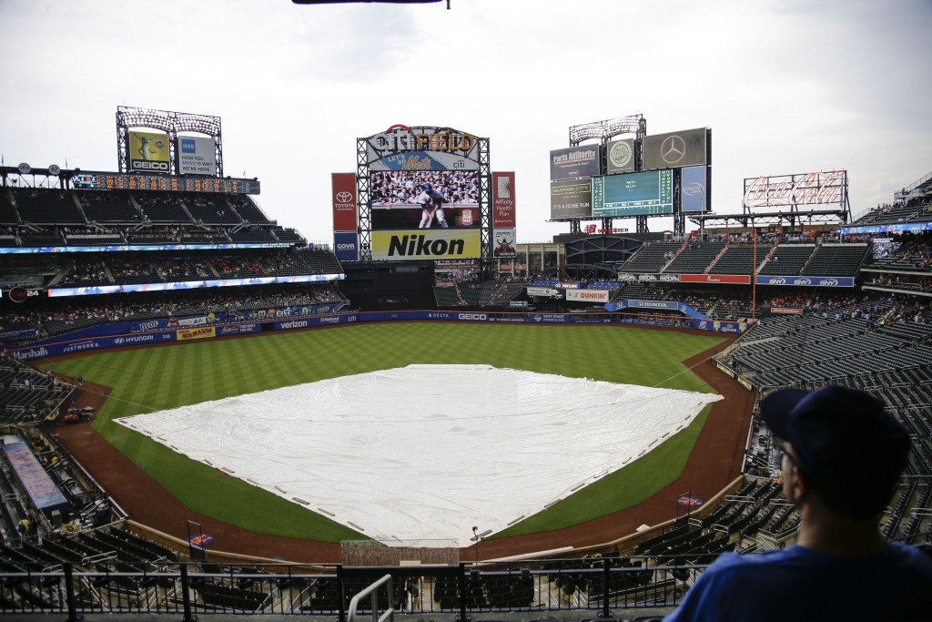 Fans wait during a rain delay in the second inning of a baseball game between the New York Mets and the Atlanta Braves, Saturday, June 29, 2019, in Ne...
