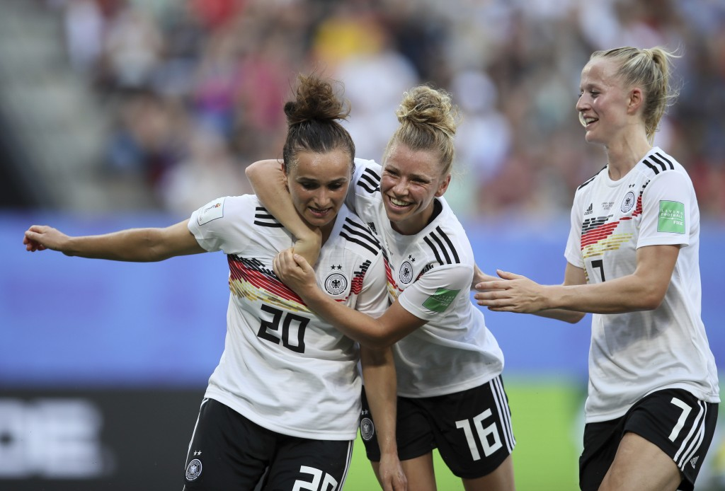 Germany's Lina Magull, left, celebrates with teammates Linda Dallmann, middle, and Lea Schueller after scoring her side's first goal during the of the...