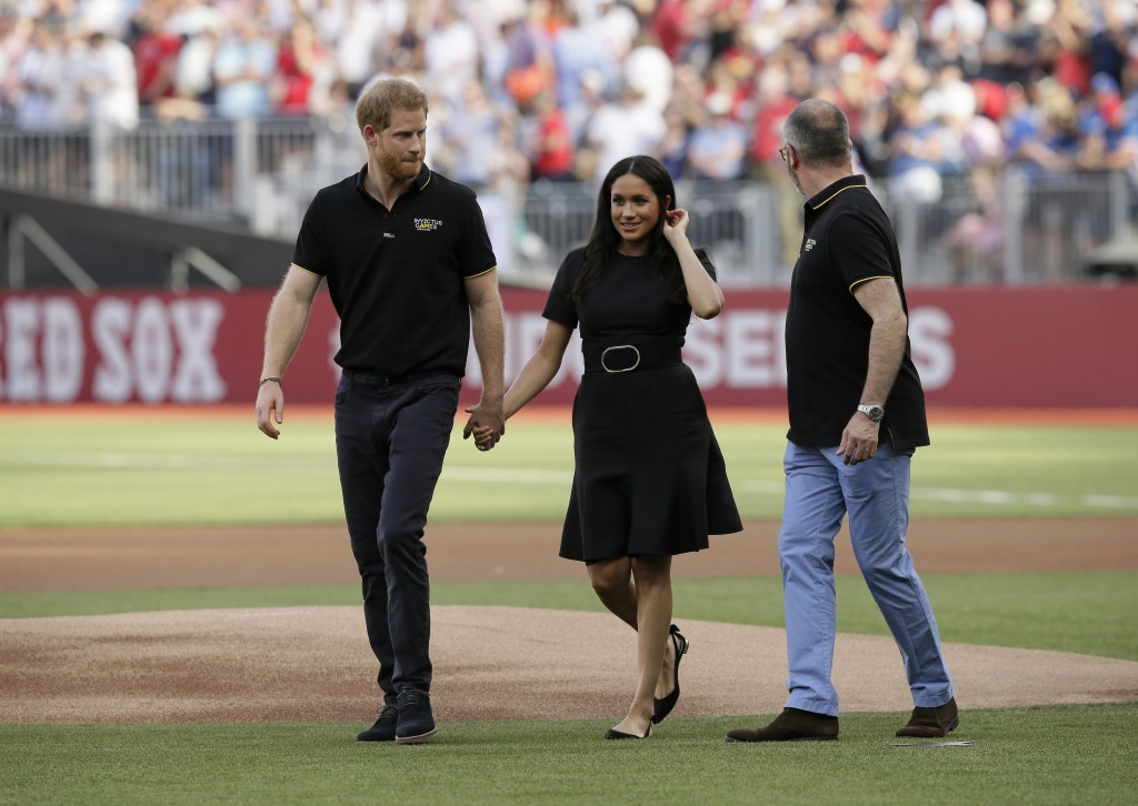 Britain's Prince Harry, left, and Meghan, Duchess of Sussex, walk off the field before a baseball game between the Boston Red Sox and the New York Yan...