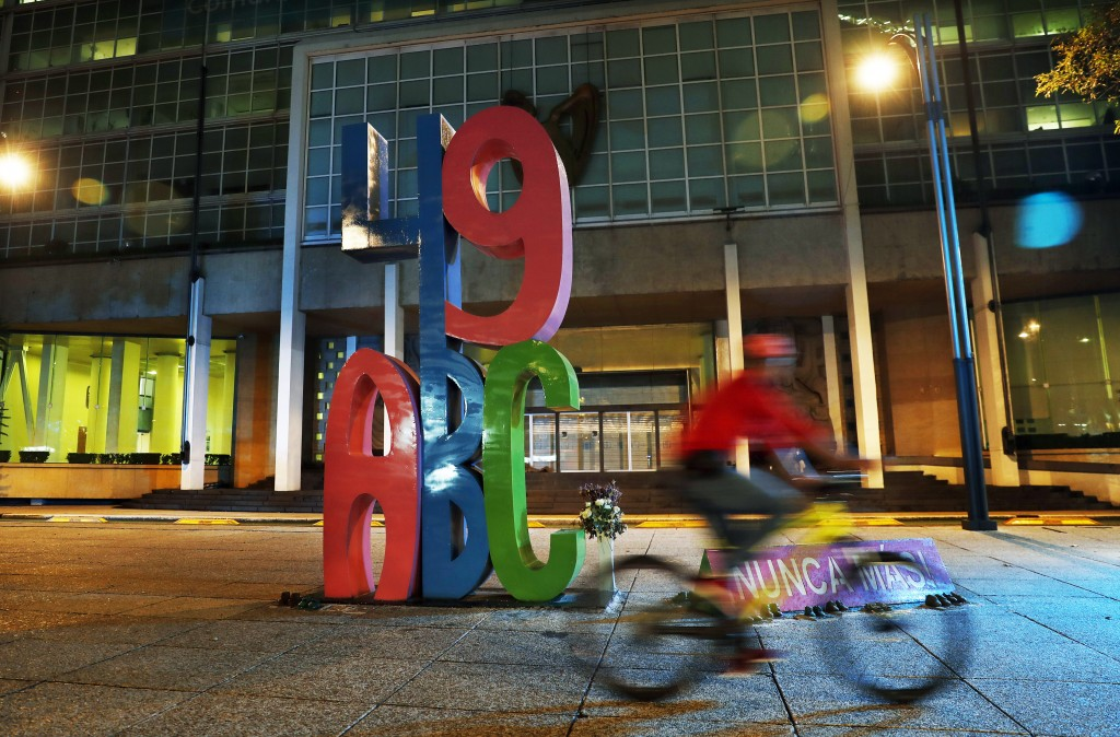 In this June 19, 2019 photo, a bicyclist pedals past a large metal installation of the letters ABC and the number 49, erected by parents of the childr...
