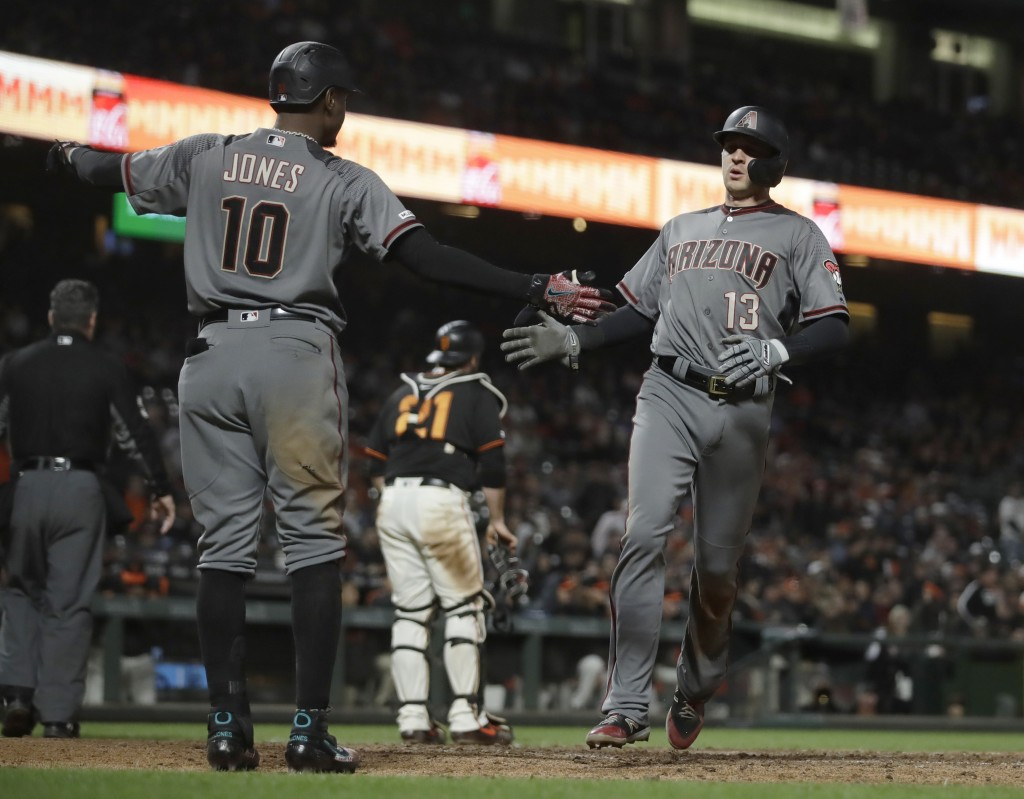 Arizona Diamondbacks' Nick Ahmed, right, is congratulated by Adam Jones (10) after scoring against the San Francisco Giants during the eighth inning o...