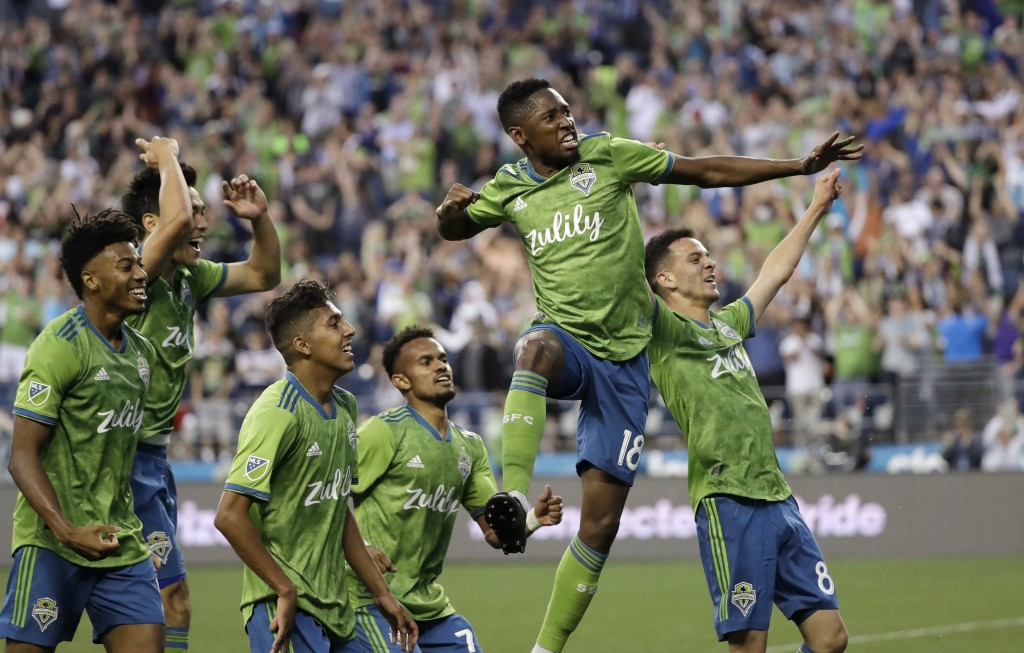 Seattle Sounders' Kelvin Leerdam (18) leaps and pumps his fist after scoring against the Vancouver Whitecaps late in the second half of an MLS soccer ...