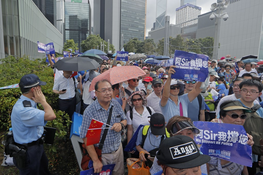 """Pro-China's supporters hold Chinese flags and placards read """"We support HK police"""" during a rally outside Legislative Council Complex in Hong Kong, Su..."""