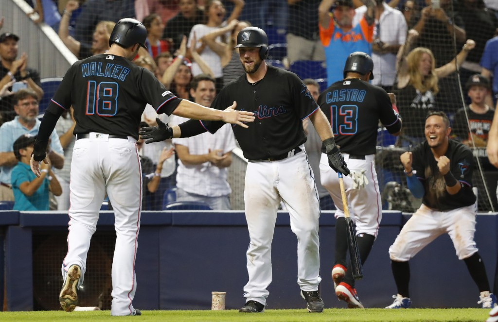 Miami Marlins' Neil Walker (18) and Starlin Castro (13) are congratulated by Bryan Holaday, second from left, and Miguel Rojas, right, after they scor...