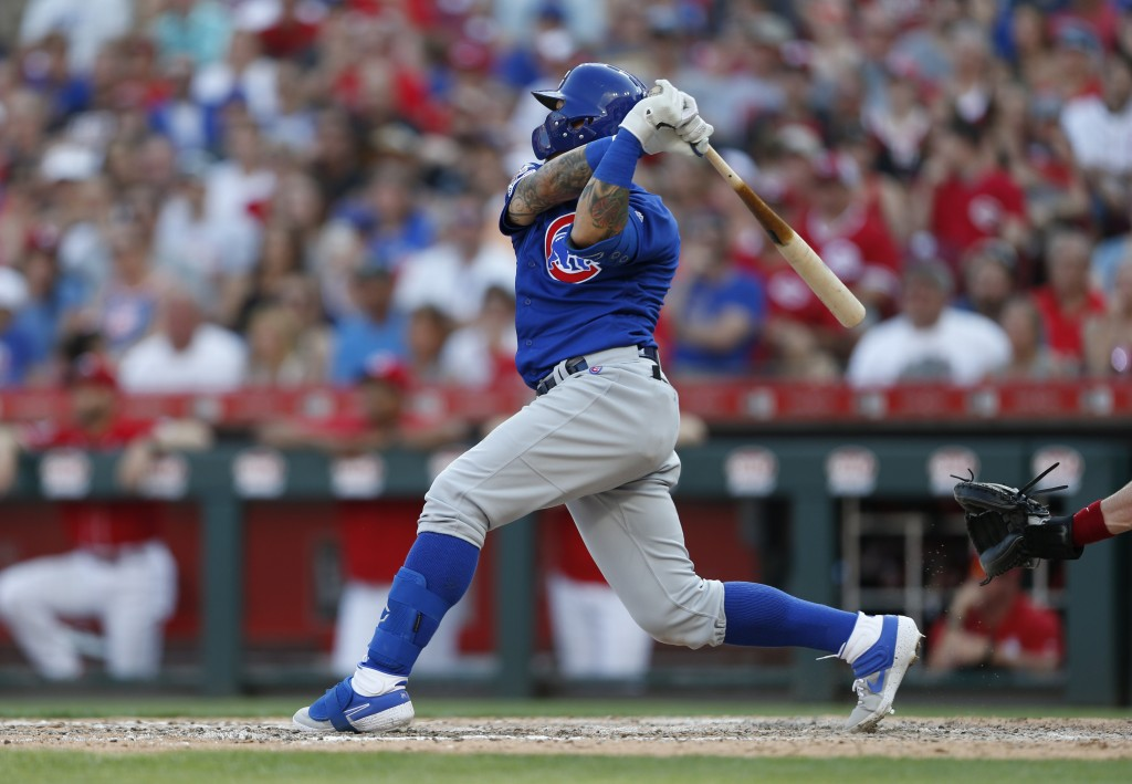Chicago Cubs' Javier Baez follows through on a grand slam home run during the eighth inning of a baseball game, Saturday, June 29, 2019, in Cincinnati...