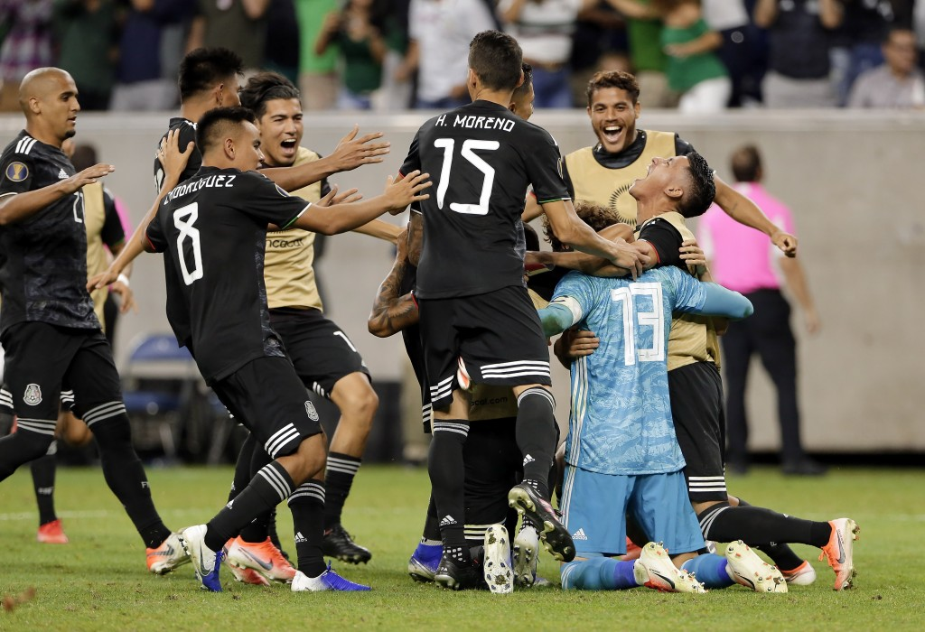Mexico players swarm goalkeeper Guillermo Ochoa (13) after he stopped the penalty kick by Costa Rica defender Keysher Fuller to give the team the win ...