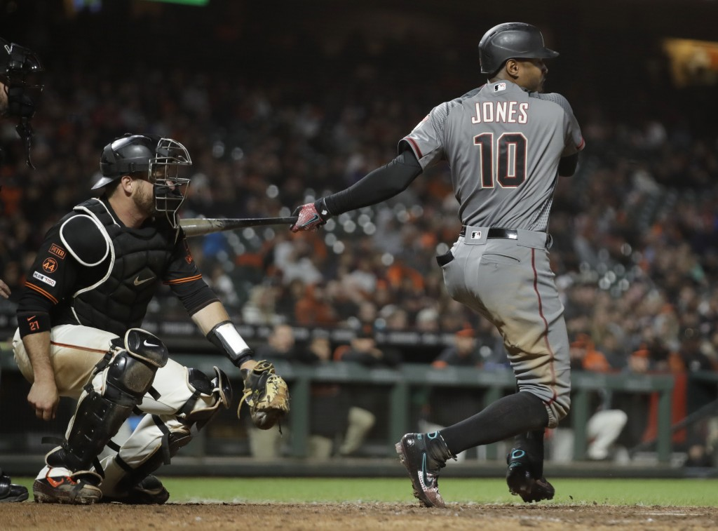 Arizona Diamondbacks' Adam Jones (10) follows through on an RBI single against the San Francisco Giants during the eighth inning of a baseball game Sa...