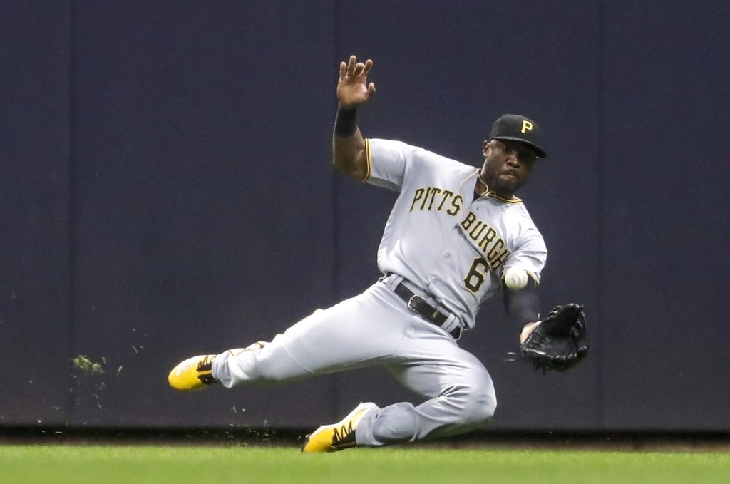 Pittsburgh Pirates' Starling Marte makes a diving catch on a ball hit by Milwaukee Brewers' Yasmani Grandal during the seventh inning of a baseball ga...