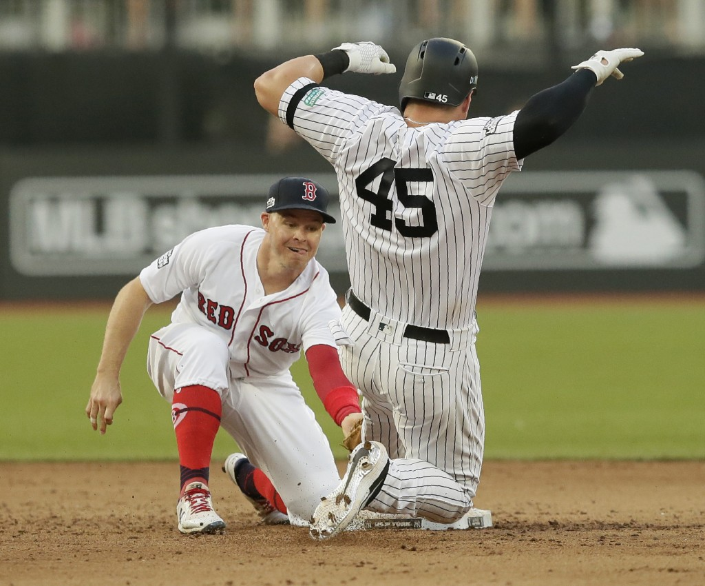 New York Yankees' Luke Voit slides safely into second base beside Boston Red Sox's Brock Holt after hitting a double during the fifth inning of a base...