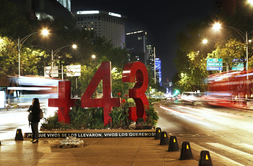 In this June 18, 2019 photo, a woman stands near a sculpture of the number 43, painted fire engine red, in a traffic median on Reforma Avenue in Mexic...