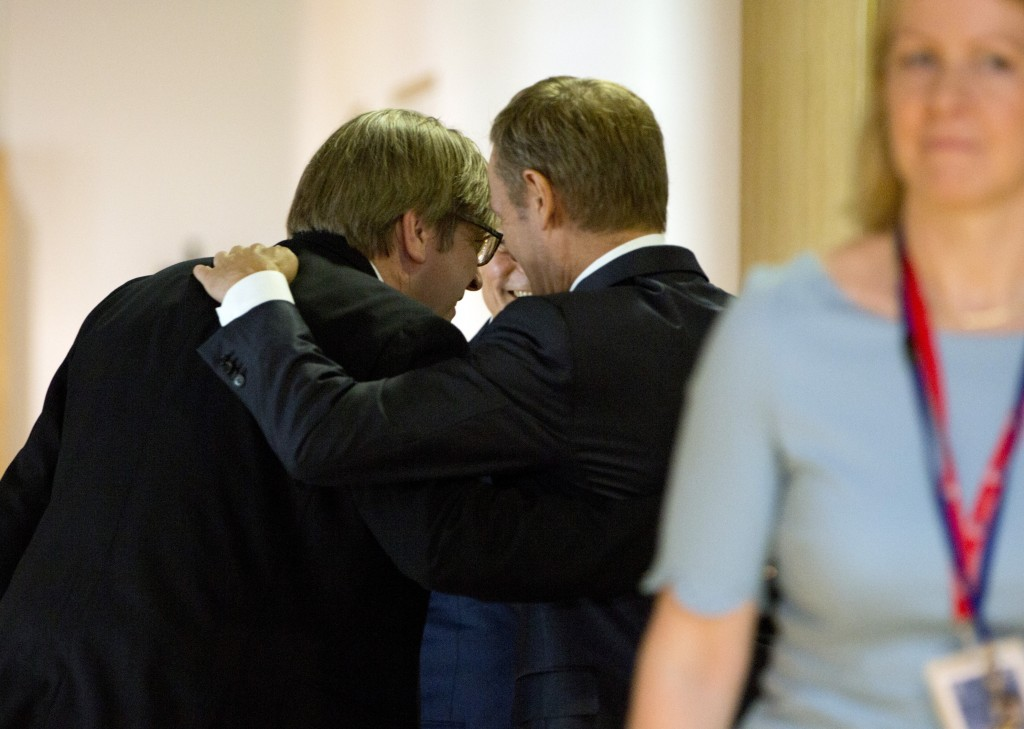 European Council President Donald Tusk, second right, huddles in a hallway with Renew Europe party members Guy Verhofstadt, left, and Daclan Ciolos, s...