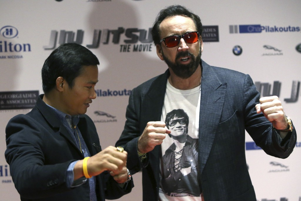 Academy award winning actor Nicolas Cage, right, and actor Jony Jaa pose to the media at a news conference for his new film Jiu Jitsu being filmed on ...