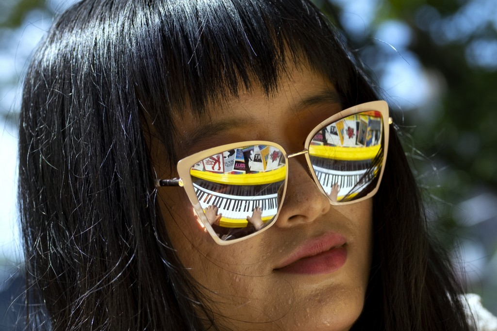 Holly Yiping Wang of New York plays a piano adorned with Broadway Playbills (reflected in her sunglasses) at the Stonewall National Monument, near the...