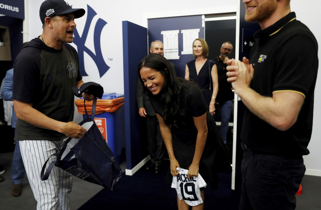 Britain's Prince Harry and Meghan, Duchess of Sussex receive a present for baby Archie as they meet players of the New York Yankees before a match aga...