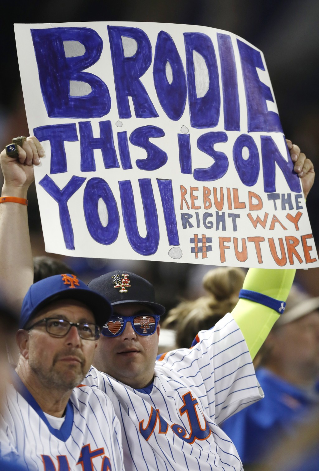 Disgruntled New York Mets fans express their sentiments with a sign for Mets general manager Brodie Van Wagenen during a baseball game against the Atl...